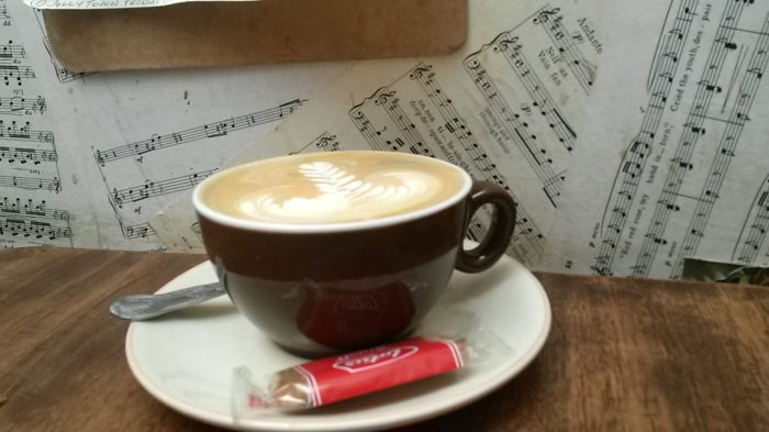 Tasting notes - A cappuccino against the  musical notation wallpaper